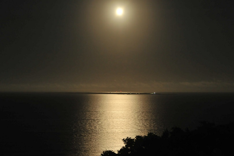 月あかりに照らされた夜の海。久高島が神々しく浮かぶ。